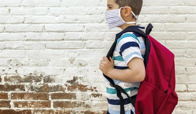 Enfant avec un sac à dos et un masque